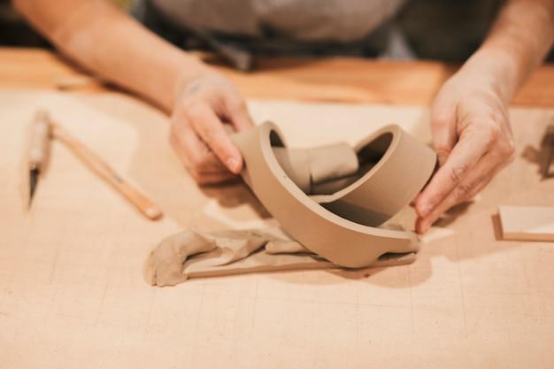 Die hand der frau, die kreatives produkt mit lehm auf hölzernem schreibtisch macht