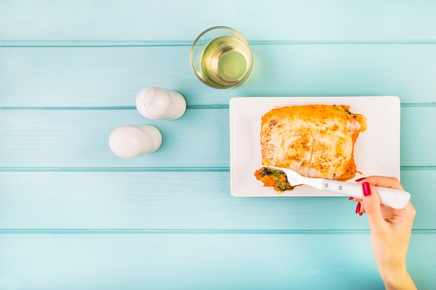 Die hand der frau, die lasagne auf hölzernem hintergrund isst