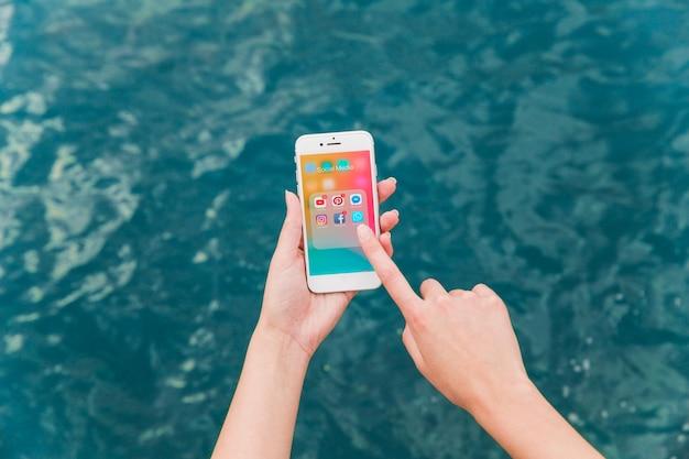 Die hand der frau, die mobiltelefon mit social media-mitteilungen auf schirm verwendet