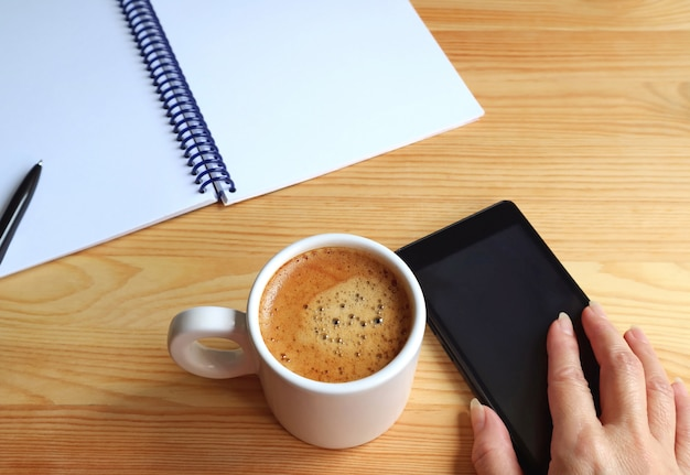 Die hand der frau, die mobiltelefon neben einer schale heißem kaffee mit notizbuch und stift auf dem arbeitsschreibtisch hält