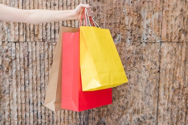 Die hand der frau, die multi farbige einkaufstaschen hält