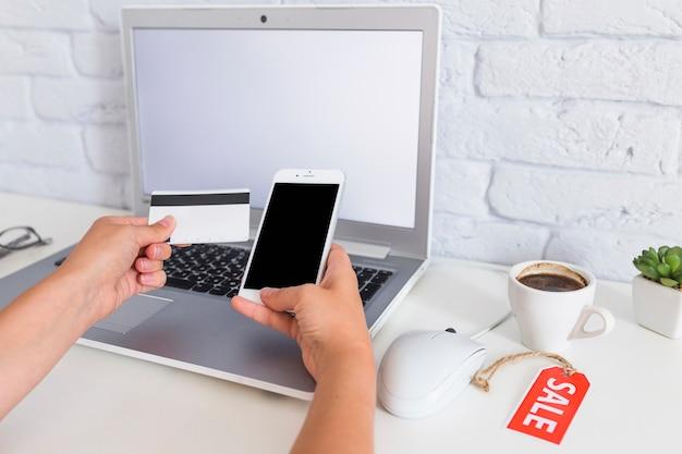 Die hand der frau, die online über handy über dem laptop kauft
