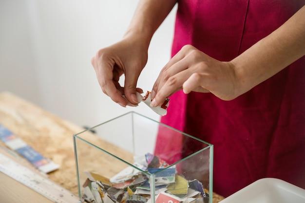 Die hand der frau, die papier in stücke zerreißt