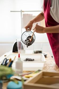 Die hand der frau, die papiermasse von der mischmaschine im behälter löscht