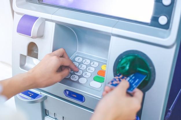 Die hand der frau, die pin / durchlaufcode auf atm / bankmaschinen-tastatur drückt