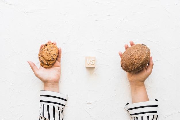 Die hand der frau, die plätzchen gegen kokosnuss über weißem strukturiertem hintergrund hält