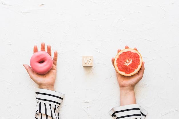 Die hand der frau, die rosa donut gegen pampelmusescheibe über strukturiertem hintergrund hält