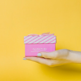 Die Hand der Frau, die rosa Kasten auf gelbem Hintergrund hält