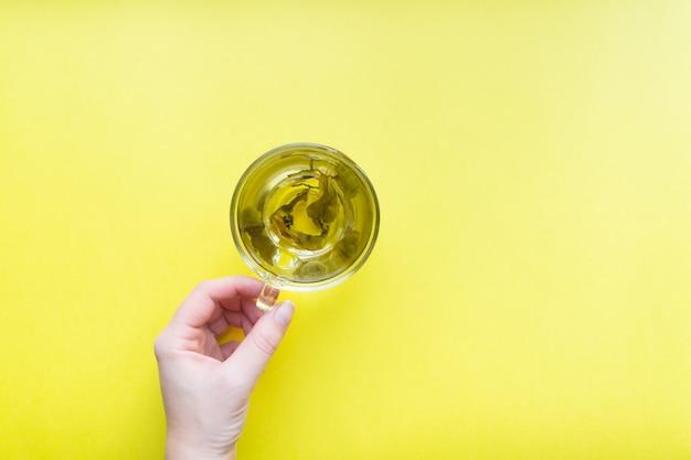 Die hand der frau, die schale grünen tee - draufsicht der minimalen ebene hält, lag auf gelbem hintergrund.