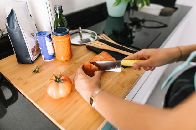 Die hand der frau, die scheiben der tomate mit messer auf küchenarbeitsplatte schneidet