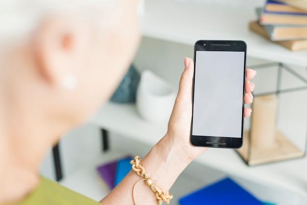Die hand der frau, die smartphone mit leerem bildschirm hält