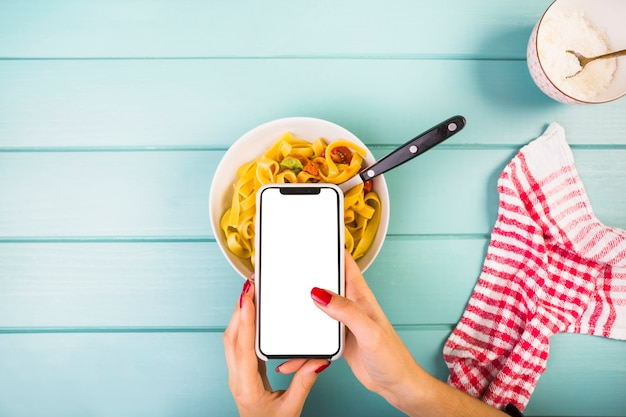 Die hand der frau, die smartphone über bandnudelnteigwaren hält
