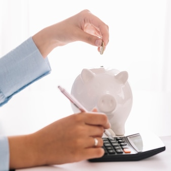 Die hand der frau, die taschenrechner beim einstecken der münze in piggybank verwendet