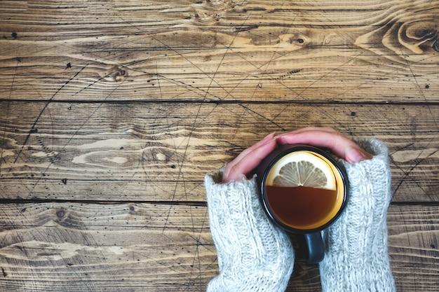 Die hand der frau, die tasse tee mit zitrone an einem kalten tag hält. holztisch. ansicht von oben.
