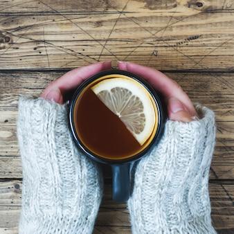 Die hand der frau, die tasse tee mit zitrone an einem kalten tag hält.
