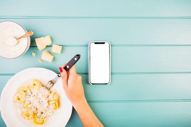 Die hand der frau, die teigwaren mit smartphone auf schreibtisch isst
