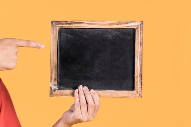 Die hand der frau, die über leeren schiefer auf gelbem hintergrund zeigt