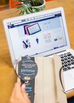 Die hand der frau, die vergrößerungsglas und lieferung nahe laptop hält