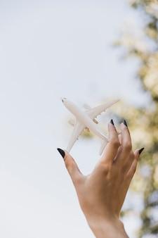 Die hand der frau, die weißes miniaturflugzeug hält