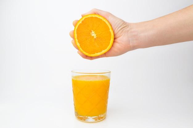 Die hand der frau drückt den saft aus der orange in ein glas.
