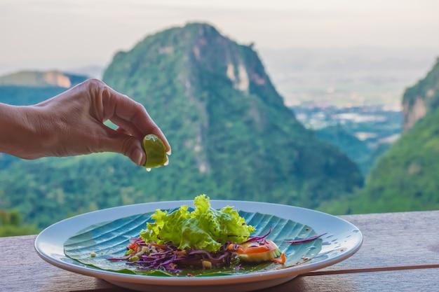 Die hand der frau drückt die zitrone in einen salat mit der schönen landschaft