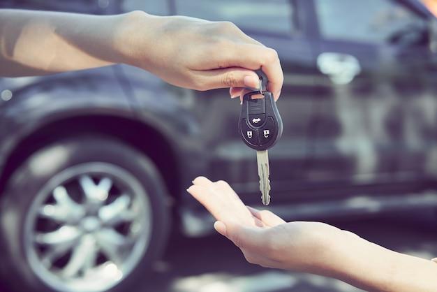 Die hand der frau geben den autoschlüssel und den unscharfen hintergrund.