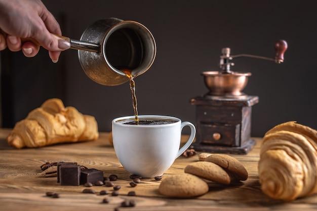 Die hand der frau gießt frischen heißen kaffee in eine weiße tasse