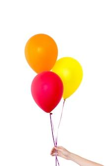 Die hand der frau hält ballone in einem weißen hintergrund