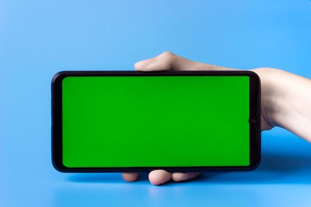 Die hand der frau hält das smartphone in einer horizontalen position mit einem grünen bildschirm auf blauem hintergrund. chroma-key. attrappe, lehrmodell, simulation