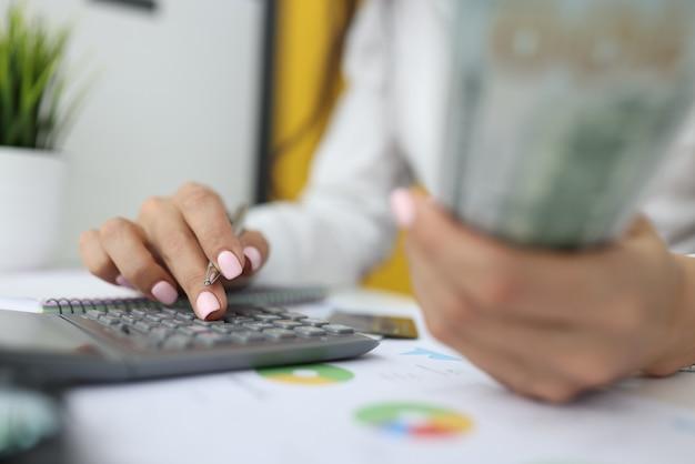 Die hand der frau hält dollar und stift mit der anderen hand und gibt zahlen auf dem taschenrechner ein.