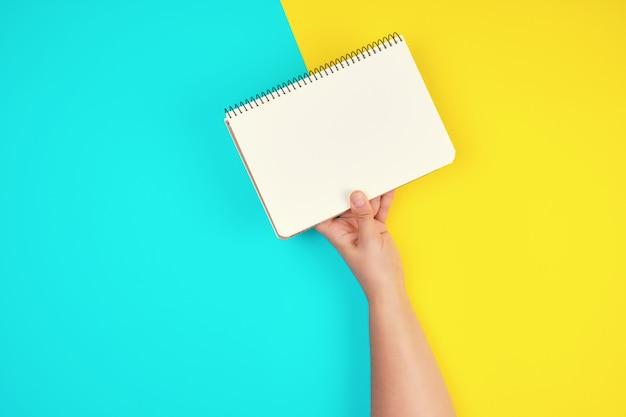 Die hand der frau hält ein offenes gewundenes notizbuch mit leeren weißen blättern