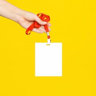 Die hand der frau hält ein sauberes weißes abzeichen an einer roten schnur an einer leuchtend gelben wand.