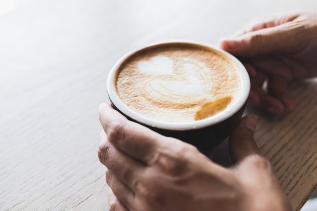 Die hand der frau hält eine heiße cappuccinokaffeetasse auf einer braunen hölzernen tabelle