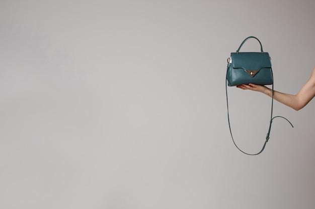 Die hand der frau hält eine neue tasche, bild lokalisiert auf weißer wand