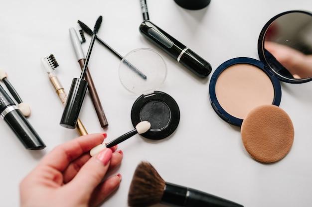 Die hand der frau hält einen pinsel für lidschatten auf hellweißer oberfläche verschiedener set-make-up-produkte: pinsel, puder, mascara, kosmetik isoliert