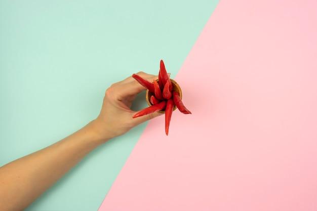 Die hand der frau hält einen waffelkegel mit roten paprikaschoten