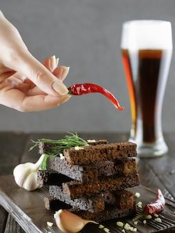 Die hand der frau hält schote des heißen roten pfeffers über roggencroutons oder biersnacks mit glas dunklem bier im hintergrund