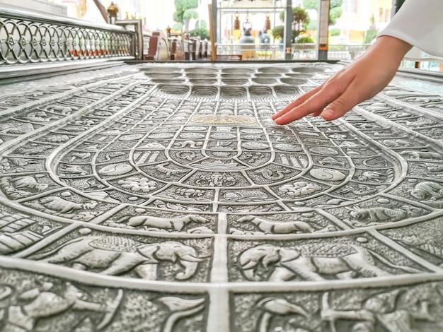 Die hand der frau ist unten. auf dem fußabdruck des buddhas, simuliert im tempel.