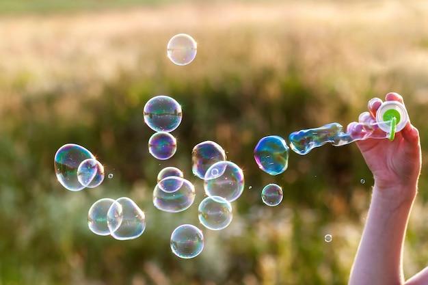 Die hand der frau mit dem schlag von bunten seifenblasen bei sonnenuntergang.