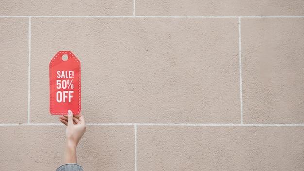 Die hand der frau mit rotem verkaufszeichen