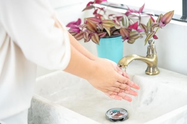 Die hand der frau öffnet den wasserhahn, um sich die hände zu waschen. um die sauberkeit zu erhalten