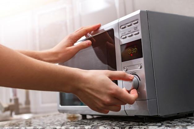 Die hand der frau schließt die tür des mikrowellenofens und stellt die zeit zum erhitzen von lebensmitteln ein