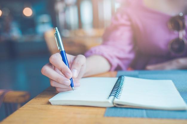 Die hand der frau schreibt mit einem stift auf ein notizbuch.