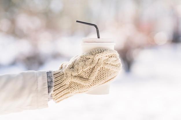 Die hand der frau, welche die handschuhe halten wegwerfkaffeetasse im winter trägt