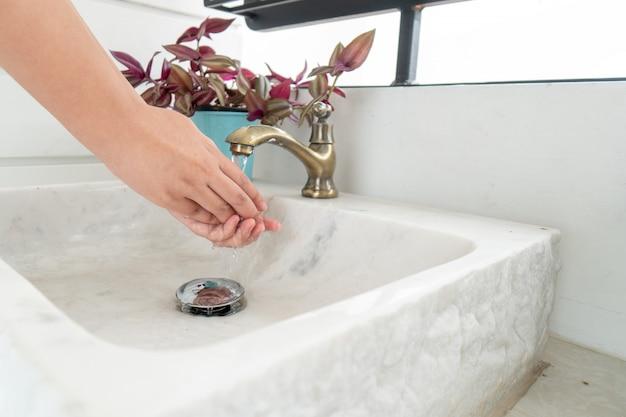 Die hand der frau wird den wasserhahn öffnen, um sich die hände zu waschen.