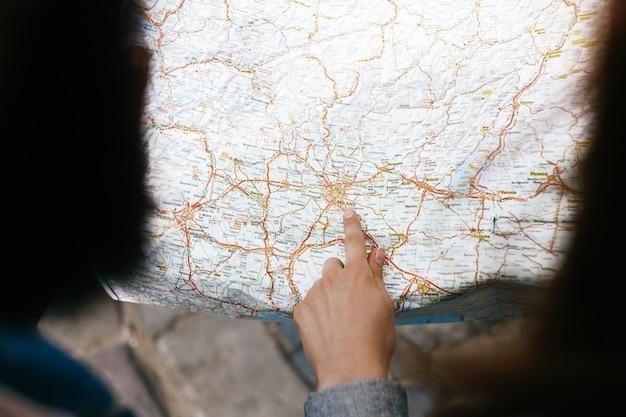 Die hand der frau zeigt an etwas in der touristischen karte