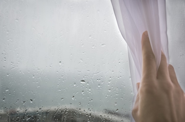 Die hand der frau zieht den vorhang vom nassen, regnerischen fenster.