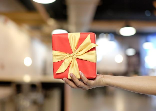 Die hand der frauen, die eine rote geschenkbox auf unschärferestauranthintergrund hält.