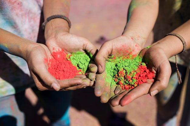 Die hand der frauen, die rote und grüne holi farben hält