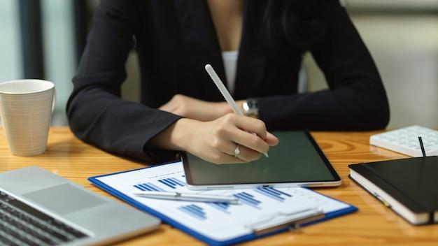 Die hand der geschäftsfrau arbeitet an einem intelligenten digitalen tablet im büro, das online am jahresabschluss arbeitet
